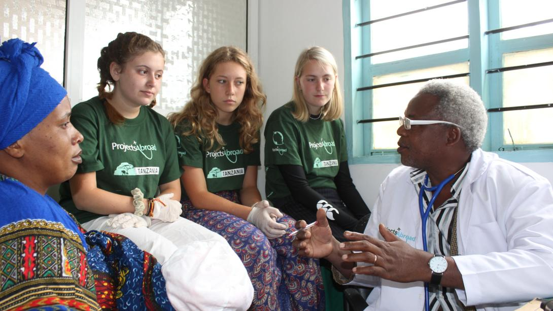 Medical interns in Tanzania listen to a doctor during a consultation with a woman